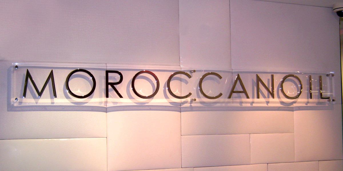 MOROCCANOIL-2_-CLEAR-POLISHED-ACRYLIC-BACKGROUND-WITH-POLISHED-STAINLESS-STEEL-LETTERS